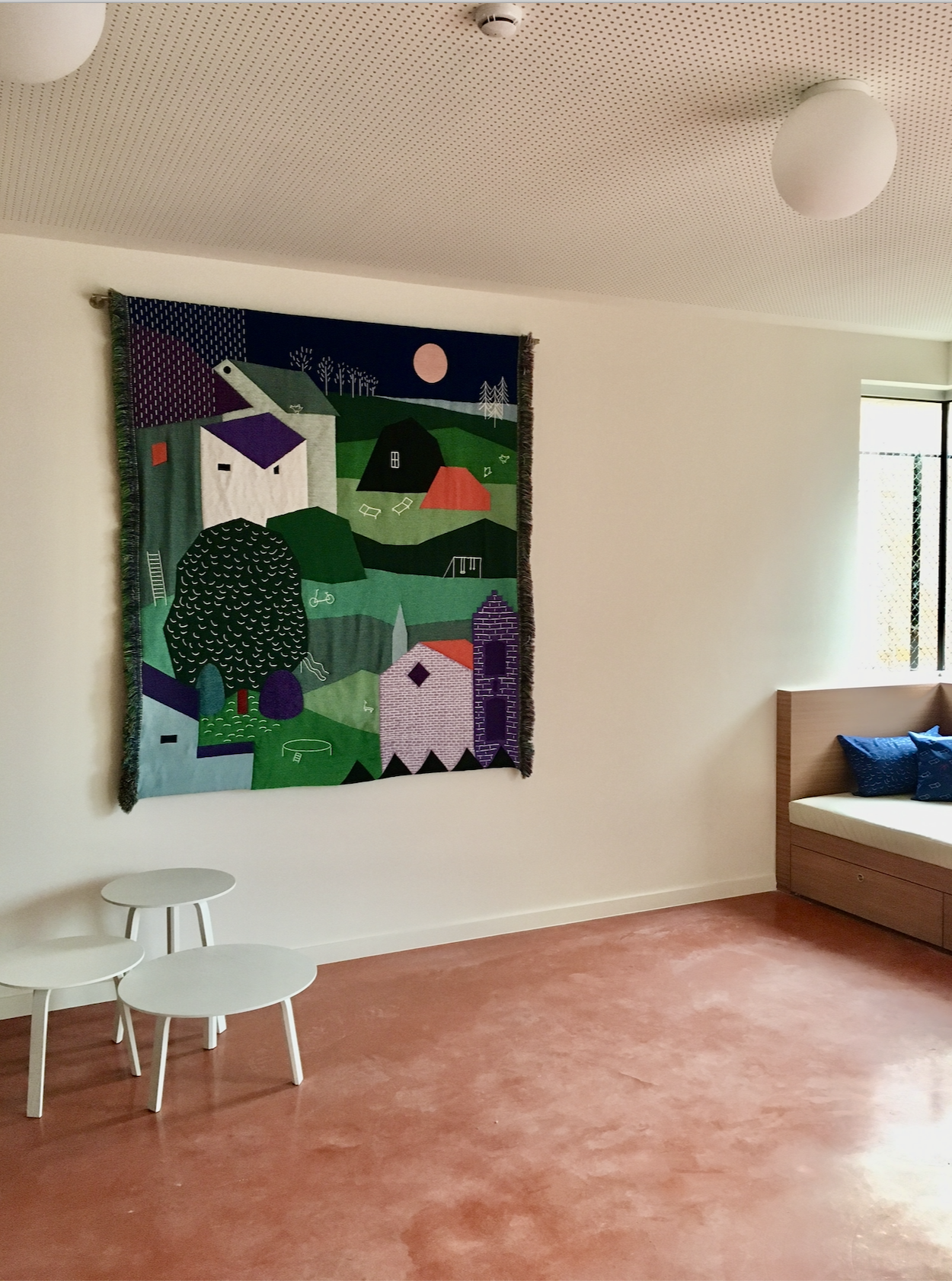 Interior with focus on woven wall hanging with landscape.